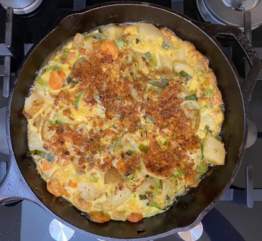 Leek, carrot and potato fritatta with soya topping on a cast iron pan