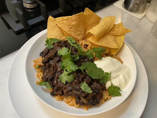 A plate with frijoles on rice, with coriander, soured cream and totopos