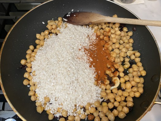 Adding rice and paprika to the pan