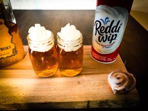 Topping the Cinnamon Roll Shot with Reddi Wip whipped cream.