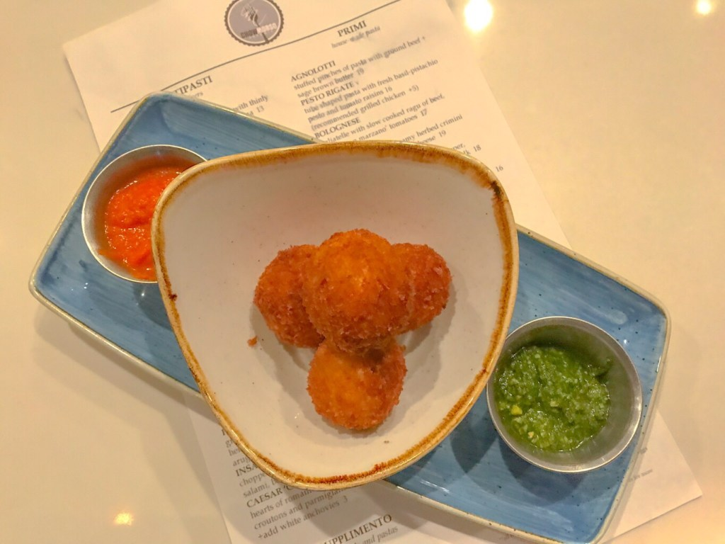 Chow Morso Osteria Arancini are lightly fried risotto balls with fontina cheese. Served with a spicy tomato sauce and basil-pistachio pesto.