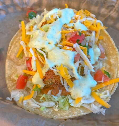 Torchy's Tacos Fried Avocado Taco made with FRIED AVOCADOS, REFRIED PINTO BEANS, PICO DE GALLO, LETTUCE & CHEDDAR JACK CHEESE WITH POBLANO SAUCE ON A CORN TORTILLA.