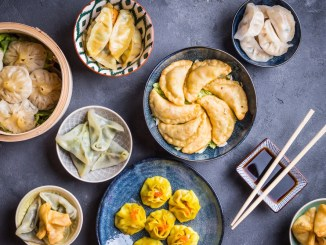 An assortment of dumplings, potstickers, and dim sum on a grey table