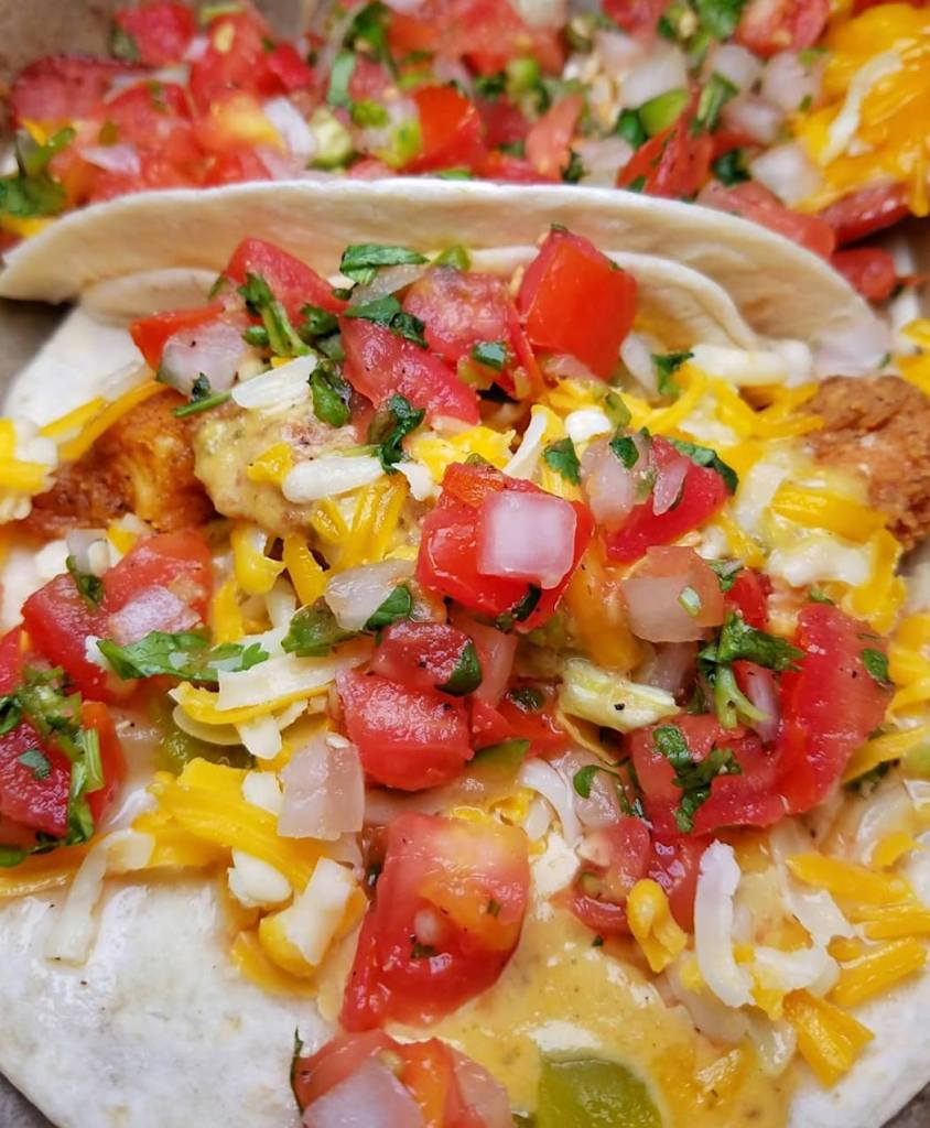 """Torchy's Tacos Trailer Park Trashy Taco made with FRIED CHICKEN, GREEN CHILES, LETTUCE, PICO DE GALLO & CHEDDAR JACK CHEESE WITH POBLANO SAUCE ON A FLOUR TORTILLA. """"GET IT TRASHY"""" – TAKE OFF THE LETTUCE & ADD AWARD WINNING GREEN CHILE QUESO!"""