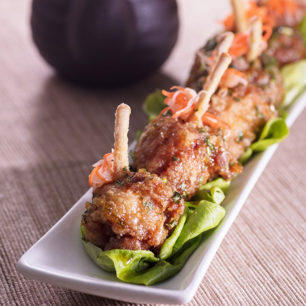 Six crispy, tender Departure lollipop wings sitting on top of butter lettuce served on a rectangular white appetizer plate.