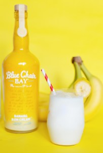 A bottle of Blue Chair Bay Bananas Rum Cream, fresh bunch of bananas, and a Bananas Foster Cocktail.