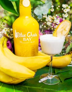 A bottle of Banana Rum Cream, a bunch of bananas, and a Bananas Foster Martini sitting on a green table cloth with flowers