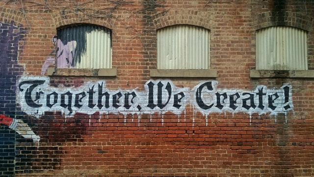"""A old red brick building we the words """"Together, We Create"""" painted on the side in street art"""