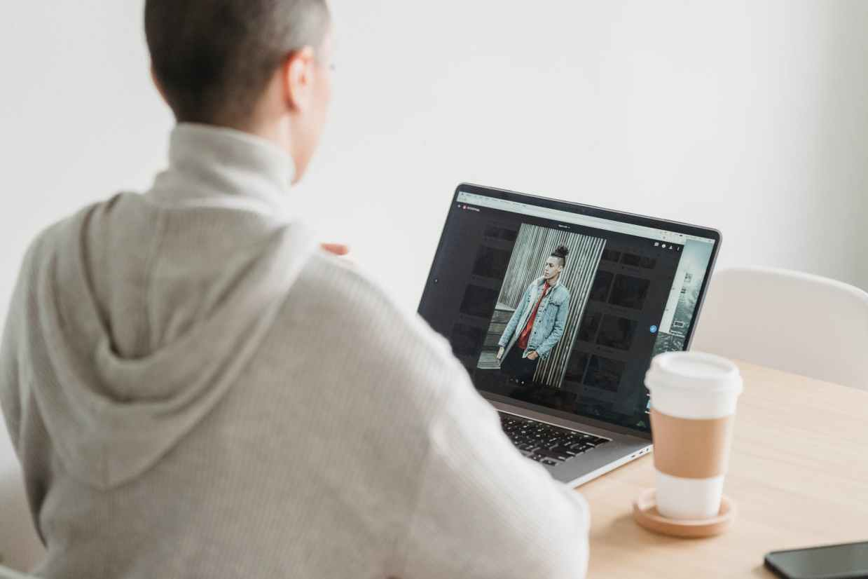 crop unrecognizable woman looking at photo on laptop screen