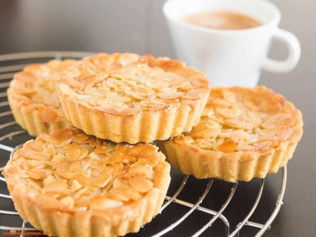 Swedish Almond Tart placed on a cooling rack, served with a cup of espresso