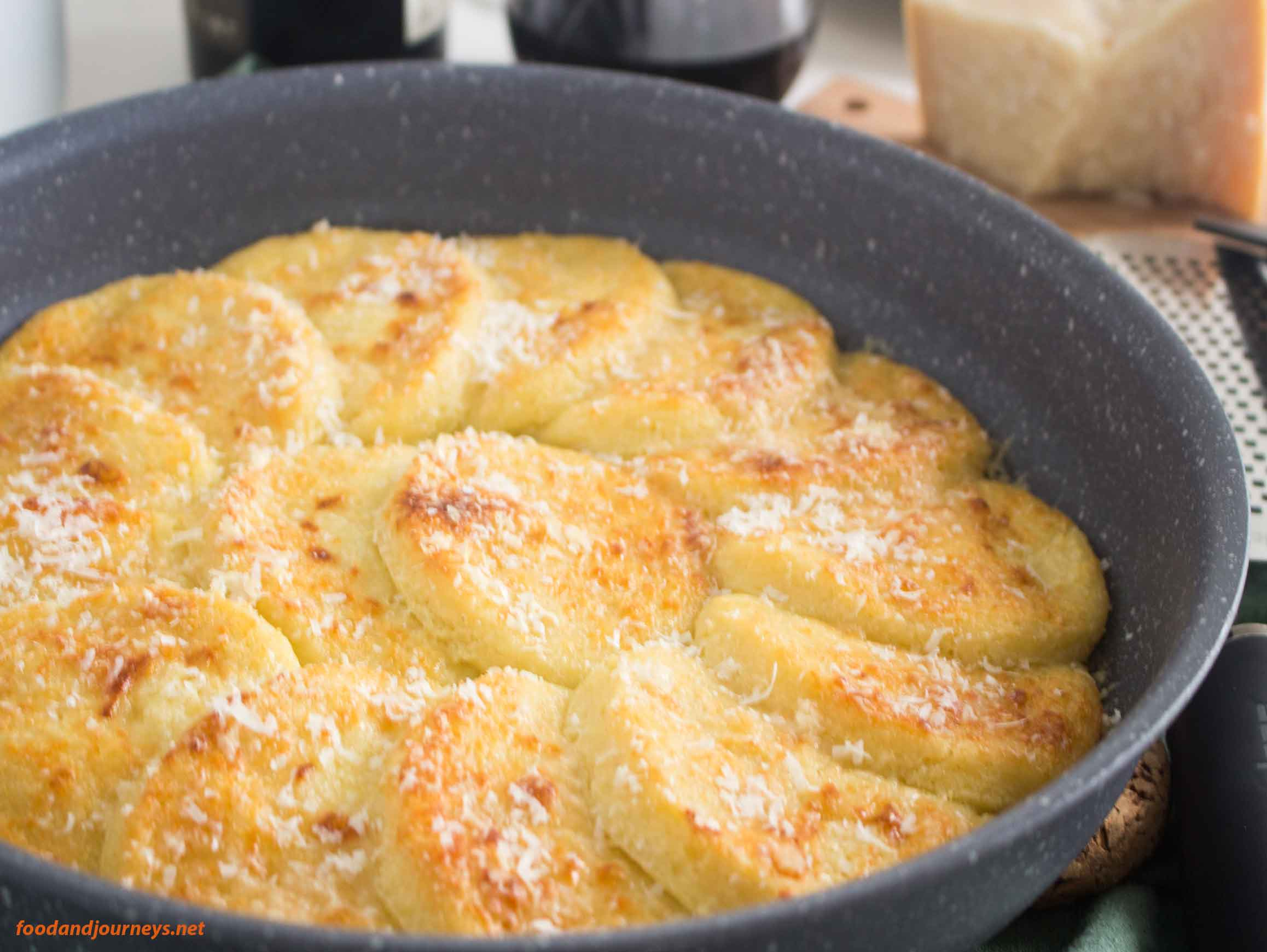 baked semolina gnocchi in a nonstick pan with cheese and wine on the side|foodandjourneys.net