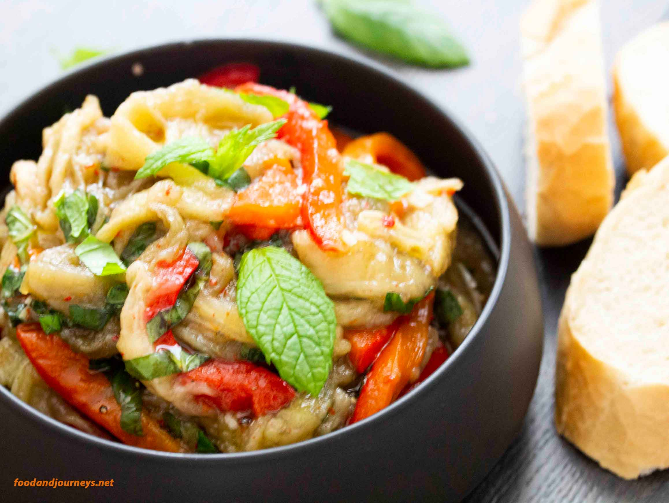 Spanish Marinated Eggplant & Peppers in a serving bowl, with slices of bread on the side