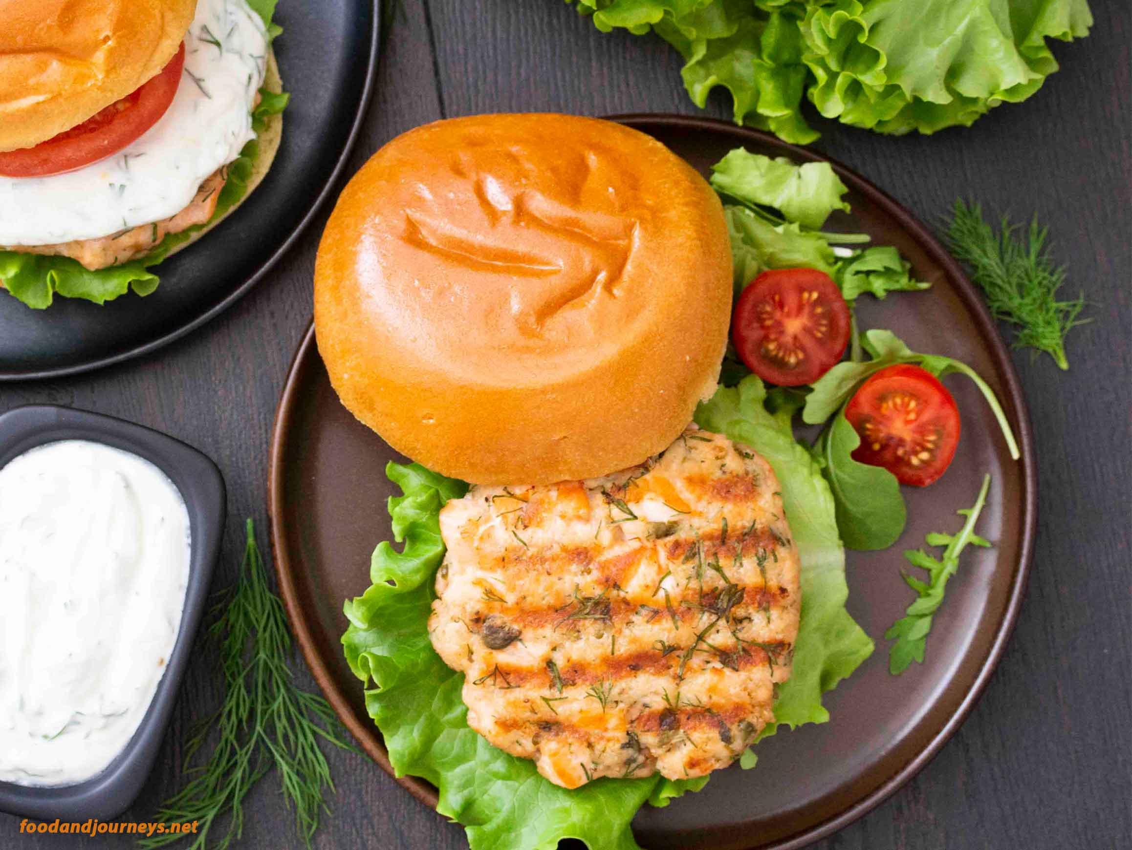 Overhead shot of Swedish Salmon Burger with Lemon Yogurt Sauce on the side.