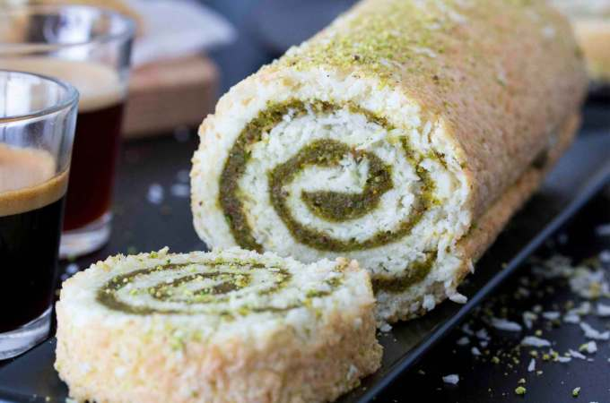 Coconut & Pistachio Cake Roll on a serving plate, with a couple of espresso cups on the side.