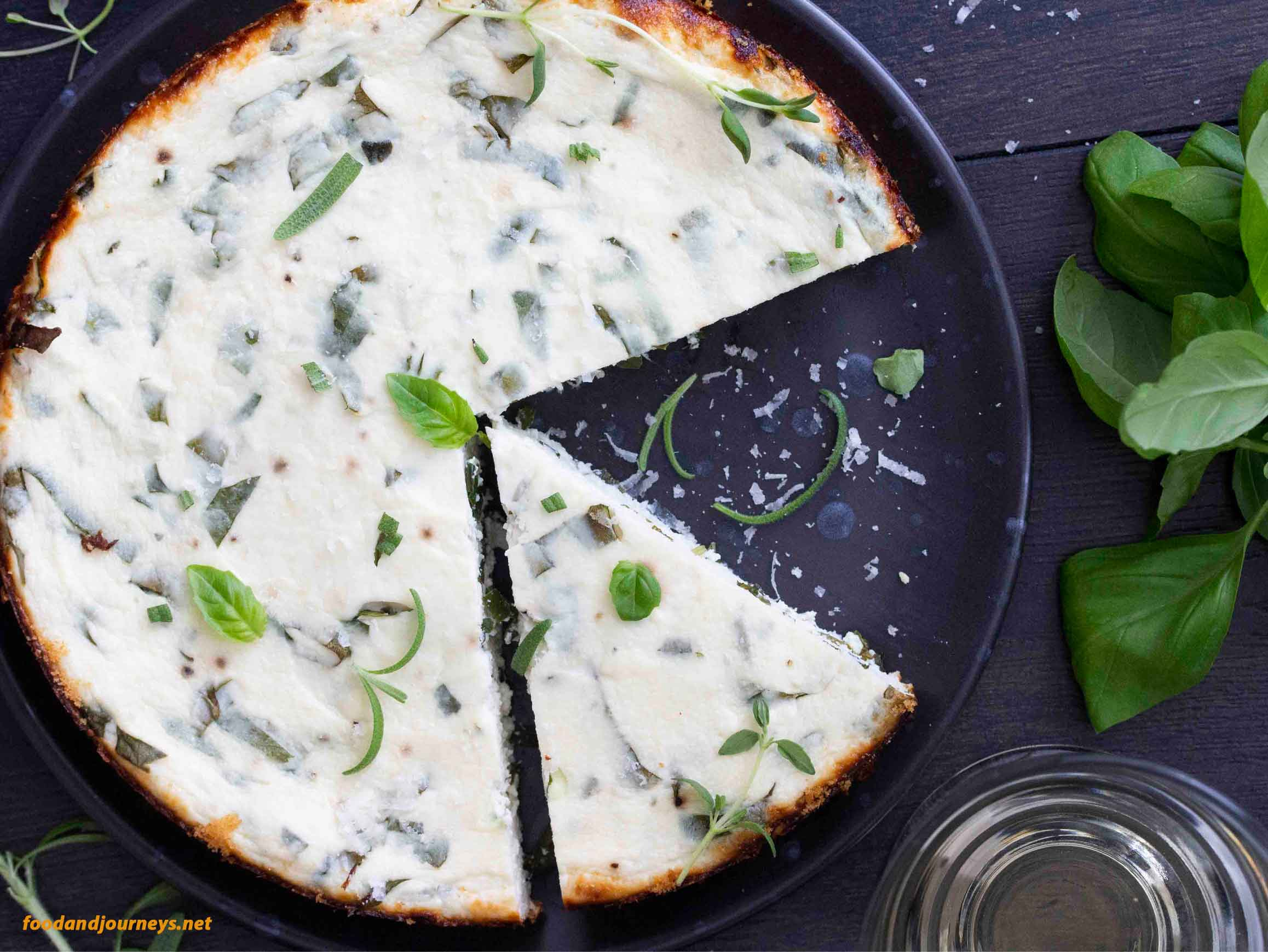 Overhead shot of Herbed Ricotta Tart, with some fresh basil on the side and a glass of white wine