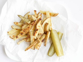 Dill Pickle Baked French Fries next to a pair of dill pickles on white serving paper