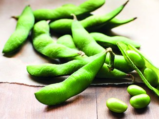 Shelled edamame on a wood background with a few shelled beans