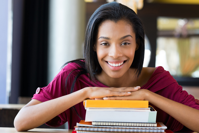 Student girl leans on stack of books