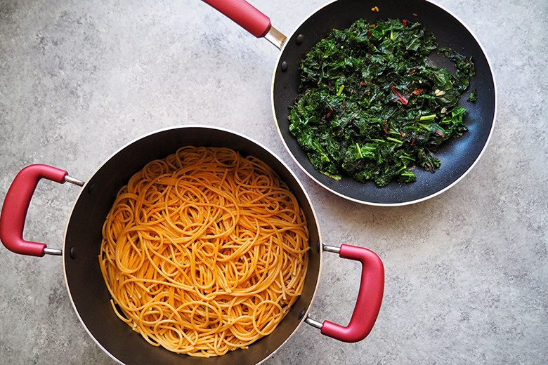 Greens in a pot and pasta in a larger two-handled pot, shot from above
