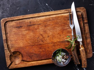 Cutting board with cutlery, rosemary and spices