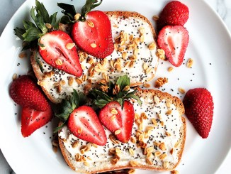 Toast with cream cheese, granola, seeds and cut strawberries