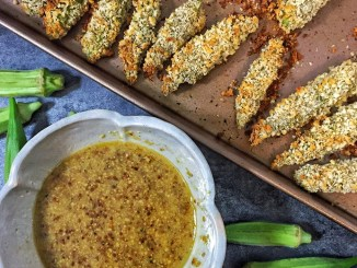 A baking tray of oven baked okra next to a bowl of honey dijon dipping sauce