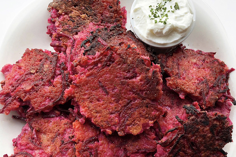 Pink Potato beet latkes with a dollop of sour cream on a plate