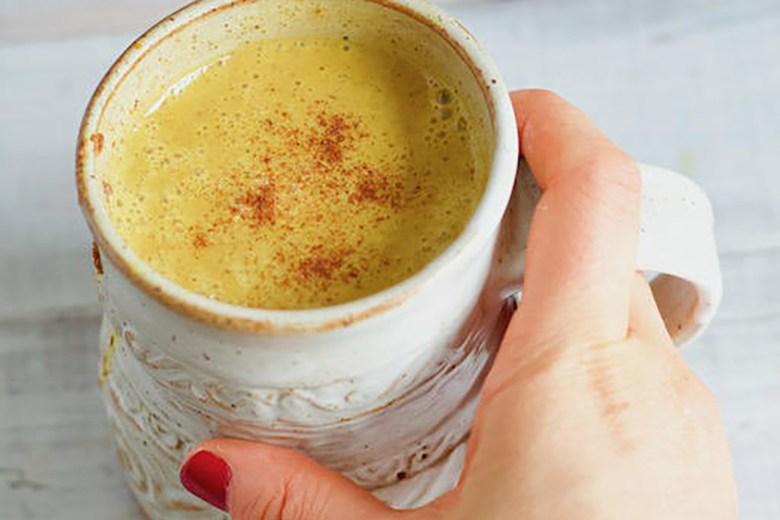 A close up shot of a hand holding a cup of Pumpkin Spice Golden Milk Latte