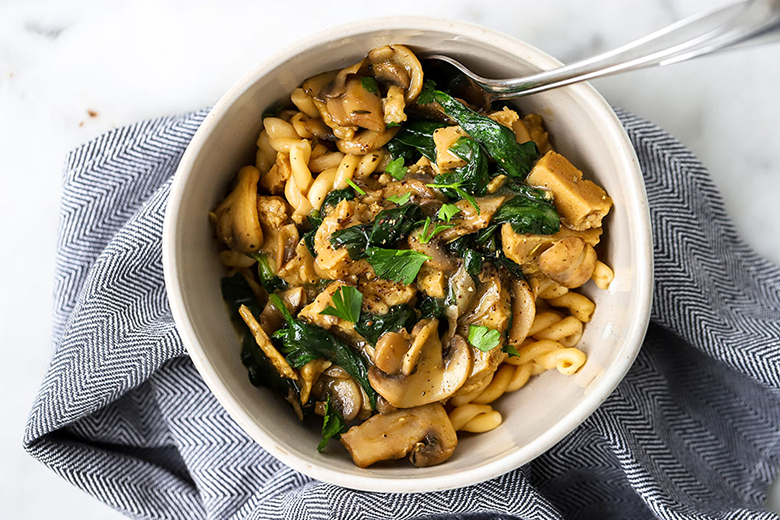 A white bowl of Quick and Easy Vegan Stroganoff sitting on a blue and white striped tea towel