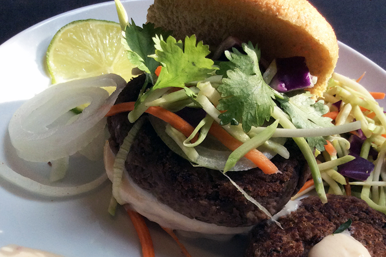 Spicy Black Bean Burger with Cilantro and YogurtSauce served on a plate with a wedge of lime