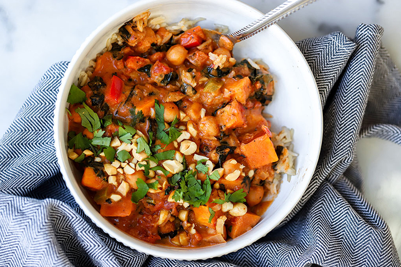 Vegan Peanut Curry with Chickpeas and Sweet Potato in a white bowl with a blue dish towel on marble countertop