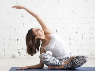 Young attractive woman in bending Sukhasana pose, white studio