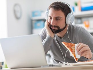 Bearded man with headphones on with a laptop and a slice of pizza