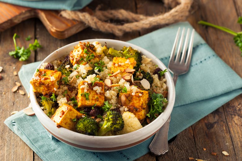 Tofu, broccoli, rice, almonds and other gluten-free foods in a bowl on top of a napkin on a wood table