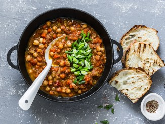 Vegetarian mushrooms chickpea stew in a iron pan and rustic grilled bread on a gray background, top view. Healthy vegetarian food concept