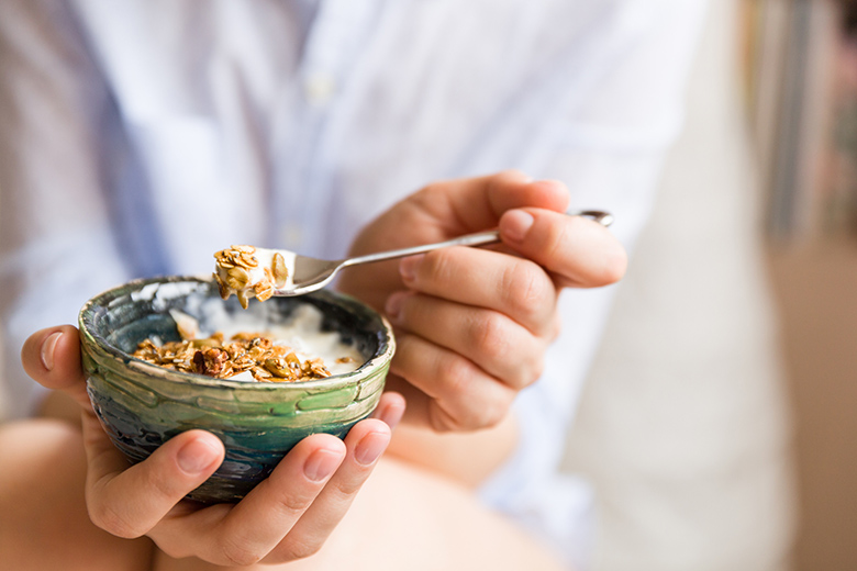 Young woman with muesli bowl. Girl eating breakfast cereals with nuts, pumpkin seeds, oats and yogurt in bowl. Girl holding homemade granola. Healthy snack or breakfast in the morning.