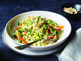 edamame slaw in white bowl with fork