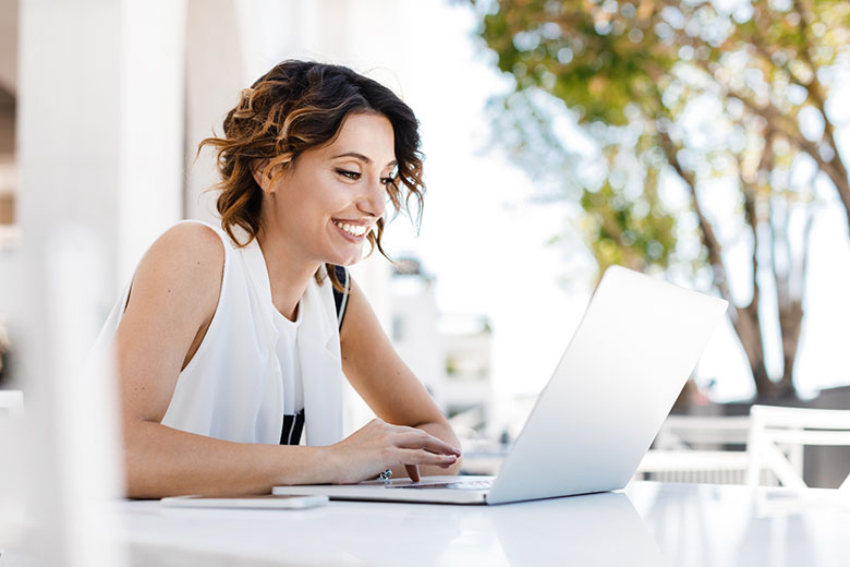 Beautiful smiling Caucasian woman sitting at cafe and working on her laptop.