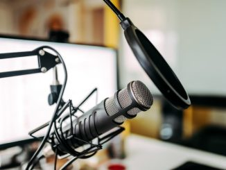 Close-up image of microphone and white computer screen in the background.