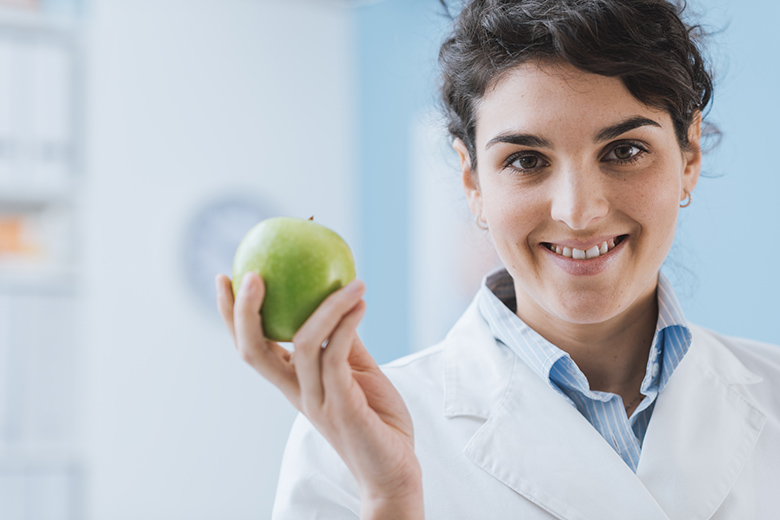 Professional nutritionist holding a fresh apple