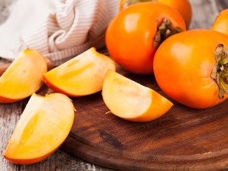 persimmons on wooden background