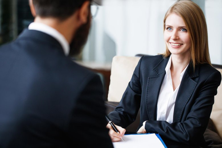 A young woman meeting with a man whose back is to the camera. She is taking notes and both are in business attire.