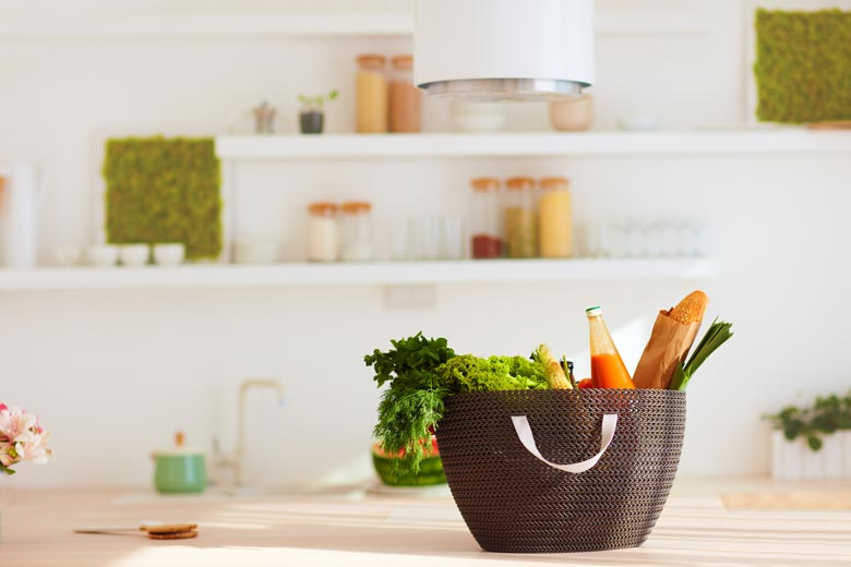 A tote full of fresh produce and bread in an open concept kitchen