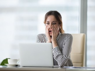 Shocked young woman looking at laptop screen. Frightened businesswoman
