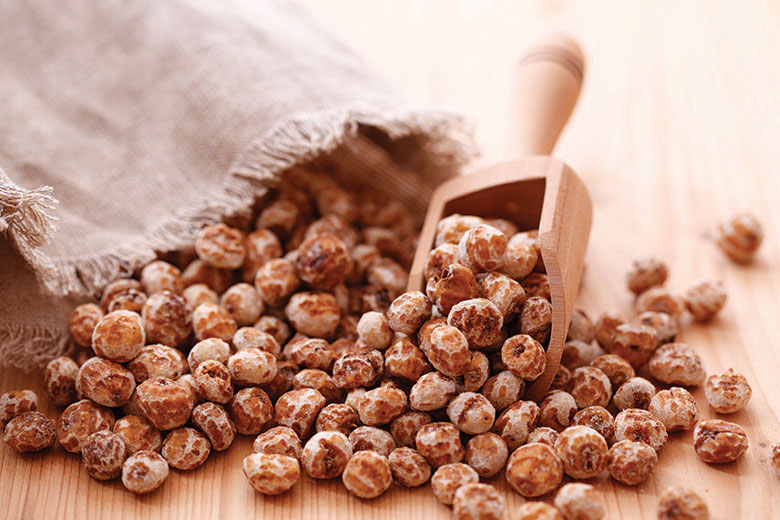 Tiger nuts spilled out onto a wood table with a wooden scoop