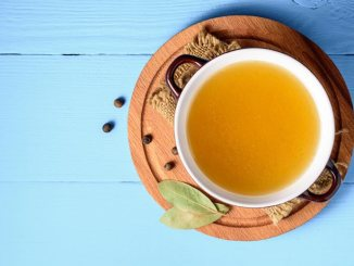 Cup of chicken stock shot from above on blue background