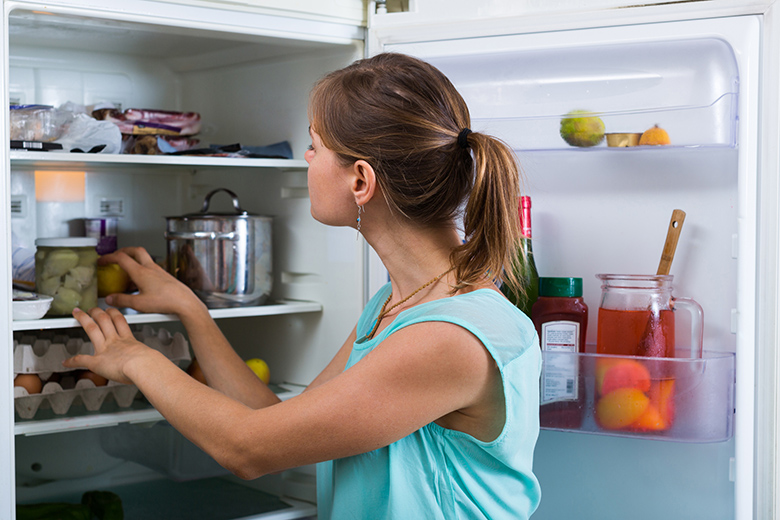 Woman near full fridge