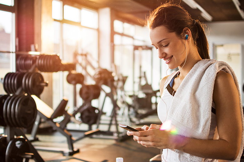 Woman dialing cellphone at gym