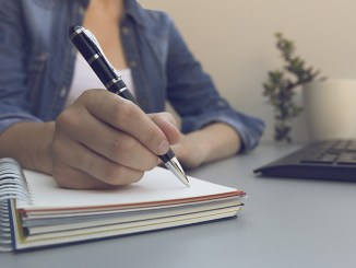 Woman's hands with pen writing on notebook. Modern grey office desk. Working, writing concept