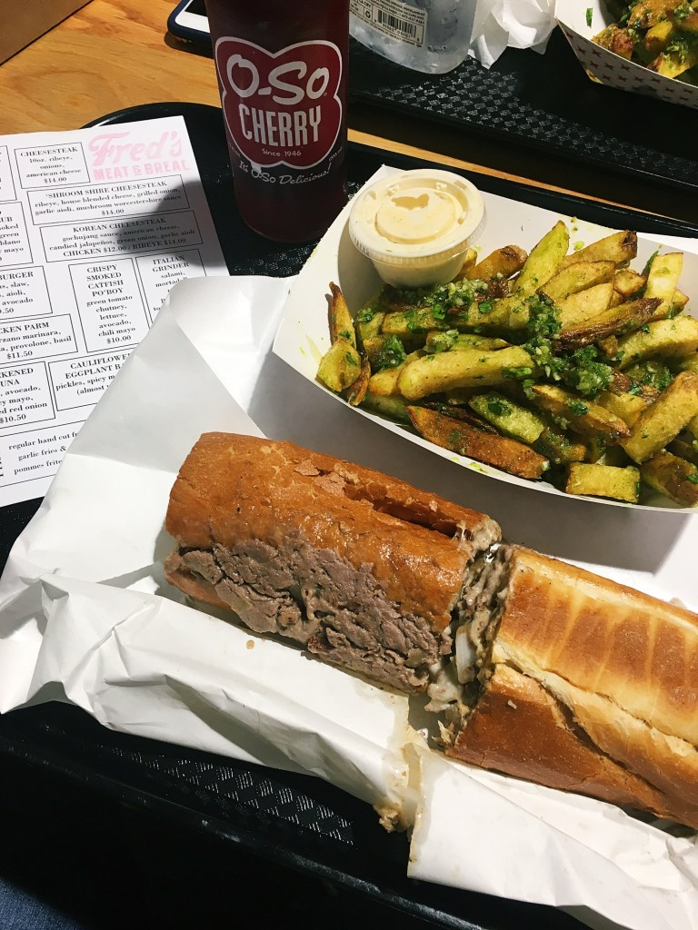 An order of the Garlic Fries, 'Shroom Shire Cheesesteak and a O-So Cherry soda